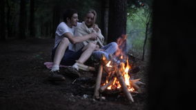 Pares jovenes que se sientan en un incendio forestal El hombre cierra a la mujer en tela escocesa y besos almacen de video