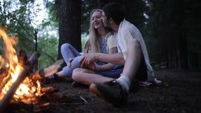 Pares jovenes que se sientan en un incendio forestal El individuo besa a la muchacha almacen de video