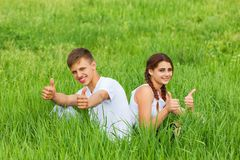 Pares jovenes que se sientan en un prado verde fotos de archivo