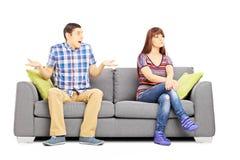 Pares jovenes que se sientan en un sofá durante una discusión imagen de archivo libre de regalías