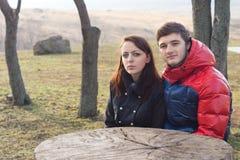 Pares jovenes que se sientan en una mesa de picnic rústica Foto de archivo libre de regalías