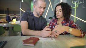 Pares jovenes que se sientan en una tabla y que miran la pantalla del smartphone haciendola clic en con sus fingeres Hombre y muj almacen de metraje de vídeo