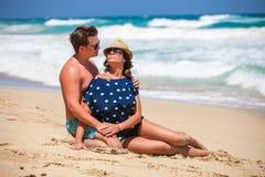 Pares jovenes que se sientan junto en una arena por el océano Foto de archivo