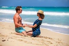 Pares jovenes que se sientan junto en una arena por el océano Imagen de archivo