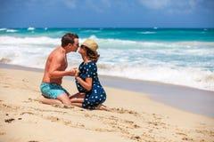 Pares jovenes que se sientan junto en una arena por el océano Fotografía de archivo