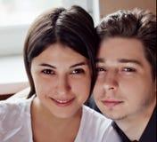 Pares jovenes que se sientan junto, mirando la leva Imagen de archivo libre de regalías