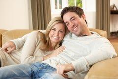 Pares jovenes que se sientan y que se relajan en el sofá Foto de archivo libre de regalías