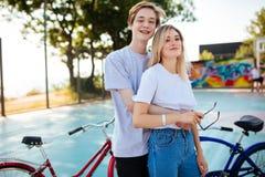 Pares jovenes que se unen y que miran feliz in camera con las bicicletas por otra parte Muchacho alegre que se coloca con bastant Fotos de archivo libres de regalías