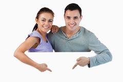 Pares jovenes que señalan en el anuncio debajo de ellos Imagen de archivo libre de regalías