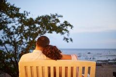 Pares jovenes que sientan y que miran el océano imagen de archivo libre de regalías