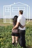 Pares jovenes que soñan sobre una casa Foto de archivo