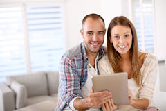 Pares jovenes que sonríen usando la tableta Fotos de archivo libres de regalías