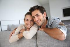 Pares jovenes que sonríen y que se inclinan en el sofá Imagenes de archivo