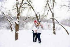 Pares jovenes que sostienen la bola de la nieve Fotos de archivo