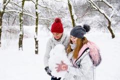 Pares jovenes que sostienen la bola de la nieve Imagen de archivo