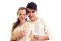 Pares jovenes que sostienen las tazas blancas Imagenes de archivo