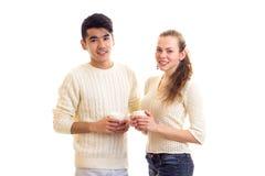 Pares jovenes que sostienen las tazas blancas Imagen de archivo