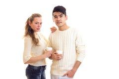 Pares jovenes que sostienen las tazas blancas Fotos de archivo libres de regalías