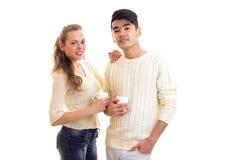 Pares jovenes que sostienen las tazas blancas Imagen de archivo libre de regalías