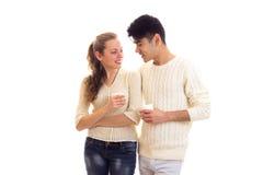Pares jovenes que sostienen las tazas blancas Fotografía de archivo libre de regalías