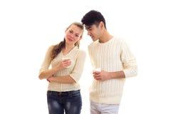 Pares jovenes que sostienen las tazas blancas Fotos de archivo