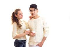 Pares jovenes que sostienen las tazas blancas Foto de archivo libre de regalías