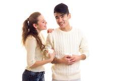 Pares jovenes que sostienen las tazas blancas Imágenes de archivo libres de regalías