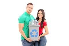 Pares jovenes que sostienen una papelera de reciclaje Foto de archivo