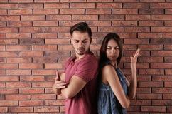Pares jovenes que tienen discusión cerca de la pared de ladrillo imagen de archivo