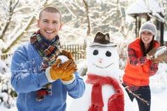 Pares jovenes que tienen lucha de la bola de nieve en jardín Fotos de archivo libres de regalías