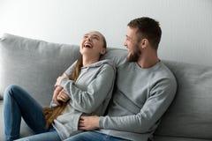 Pares jovenes que tienen relajación de risa de la diversión en casa en el sofá Foto de archivo libre de regalías