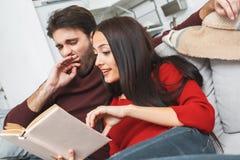 Pares jovenes que tienen romántico igualando en casa el libro de lectura de la mujer imagenes de archivo
