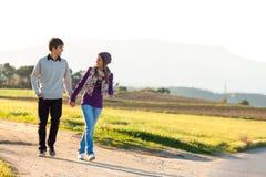 Pares jovenes que tienen un paseo en campo. Imagen de archivo