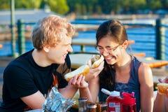 Pares jovenes que tienen una comida campestre de la diversión por el lago Fotos de archivo