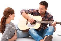Pares jovenes que tocan la guitarra Fotos de archivo libres de regalías