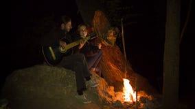 Pares jovenes que tocan la guitarra en la hoguera almacen de video