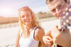 Pares jovenes que tocan la guitarra en la playa en amor Fotografía de archivo