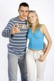 Pares jovenes que toman el cuadro por el teléfono/el palmtop Imagen de archivo libre de regalías