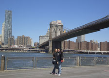 Pares jovenes que toman el selfie en el frente del puente de Brooklyn Imágenes de archivo libres de regalías