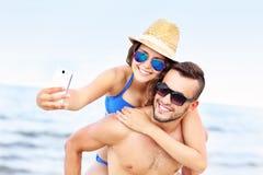 Pares jovenes que toman el selfie en la playa Fotografía de archivo