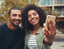 Pares jovenes que toman el selfie en el tel?fono m?vil fotografía de archivo libre de regalías