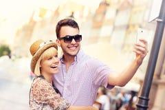 Pares jovenes que toman el selfie mientras que hace turismo la ciudad Fotografía de archivo