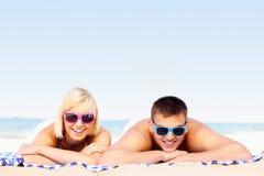 Pares jovenes que toman el sol en la playa Fotos de archivo
