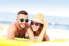 Pares jovenes que toman el sol en la playa foto de archivo libre de regalías