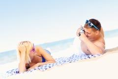 Pares jovenes que toman imágenes en la playa foto de archivo libre de regalías