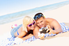 Pares jovenes que toman imágenes en la playa foto de archivo
