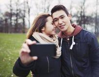 Pares jovenes que toman imágenes usando un teléfono elegante Imagenes de archivo