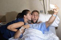 Pares jovenes que toman la foto del selfie en el sitio de hospital con el hombre que miente en cama de la clínica Fotos de archivo