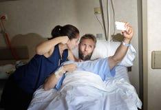 Pares jovenes que toman la foto del selfie en el sitio de hospital con el hombre que miente en cama de la clínica Imagenes de archivo