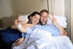 Pares jovenes que toman la foto del selfie en el sitio de hospital con el hombre que miente en cama de la clínica Fotografía de archivo